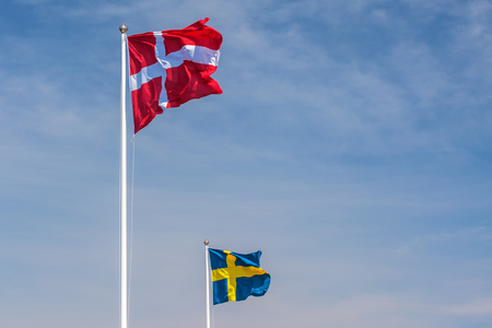 european culture: The official flags of Denmark and Sweden in front of a blue sky
