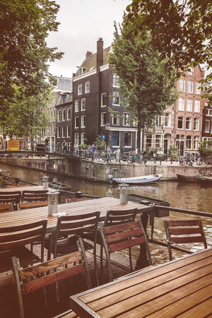dutch: AMSTERDAM, THE NETHERLANDS - AUGUST 2, 2016: Retro styled image of empty restaurant tables in front of a canal with tourists walking by in Amsterdam, The Netherlands Editorial