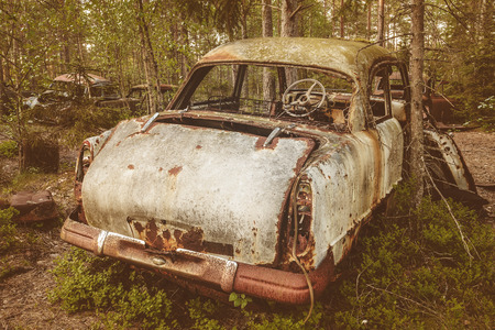 scrap: Retro styled image of an old rusted and weathered scrap car in a forest