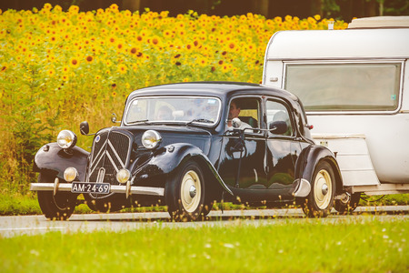 DIEREN, THE NETHERLANDS - AUGUST 14, 2016: Retro styled image of a Vintage Citroen Traction Avant with caravan on a local road in front of a field with blooming sunflowers in Dieren, The Netherlands Editorial