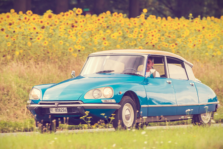old car: DIEREN, THE NETHERLANDS - AUGUST 14, 2016: Retro styled image of a Vintage Citroen DS on a local road in front of a field with blooming sunflowers in Dieren, The Netherlands