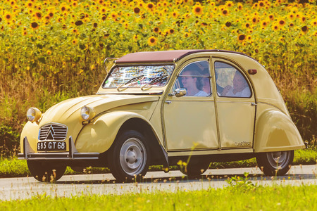 70s: DIEREN, THE NETHERLANDS - AUGUST 12, 2016: Retro styled image of a Vintage Citroen 2CV on a local road in front of a field with blooming sunflowers in Dieren, The Netherlands