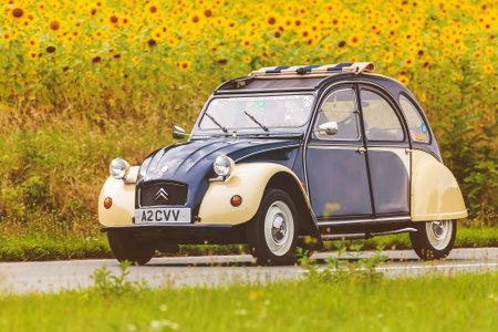 champ de fleurs: DIEREN, PAYS-BAS - 14 août 2016: Rétro image d'une Citroen 2CV Vintage style sur une route locale en face d'un champ avec la floraison des tournesols à Dieren, Pays-Bas