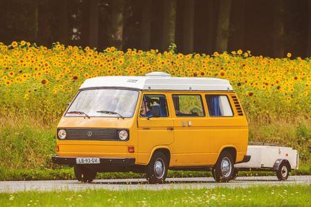 DIEREN, THE NETHERLANDS - AUGUST 14, 2016: Retro styled image of a Vintage Volkswagen Transporter with popup camper on a local road in front of a field with blooming sunflowers in Dieren, The Netherlands