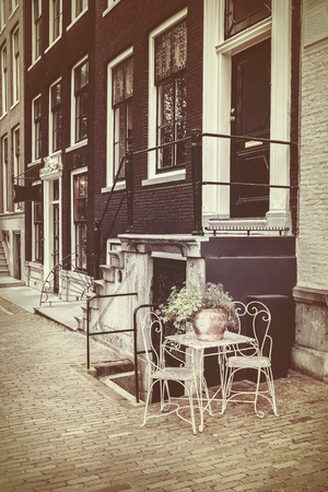 canal houses: Retro styled image of Amsterdam canal houses with bistro set in front