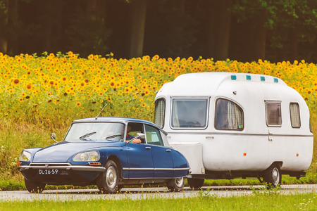 70s: DIEREN, THE NETHERLANDS - AUGUST 14, 2016: Retro styled image of a Vintage Citroen DS with caravan on a local road in front of a field with blooming sunflowers in Dieren, The Netherlands Editorial