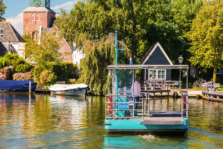 NIGTEVECHT, THE NETHERLANDS - AUGUST 23, 2016: Bicycle ferry powered by solar panels passing the river vecht in Nigtevecht, The Netherlands Editorial