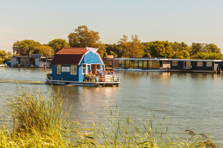 house float on water: DIEREN, THE NETHERLANDS - AUGUST 23, 2016: Recreational houseboat used for vacations passing other houseboats on the river Vecht in Weesp, The Netherlands
