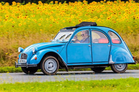 oldtimer: DIEREN, THE NETHERLANDS - AUGUST 12, 2016: Retro styled image of a Vintage Citroen 2CV on a local road in front of a field with blooming sunflowers in Dieren, The Netherlands