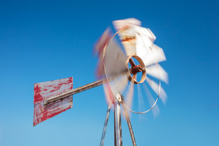 water turbine: Old weathered steel windmill in front of a clear blue sky Stock Photo