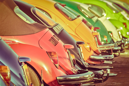 Retro styled image of a row of colorful classic cars