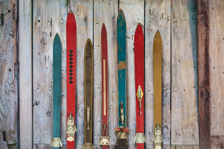 Collection of vintage wooden weathered skis in front of an old barn