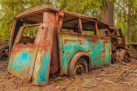 Wreck of a colorful rusted old transport bus in a forest Stock Photo