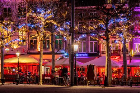 netherlands: MAASTRICHT, THE NETHERLANDS - NOVEMBER 22, 2016: Bars and restaurants with christmas lights on the famous Vrijthof square in Maastricht, The Netherlands Editorial
