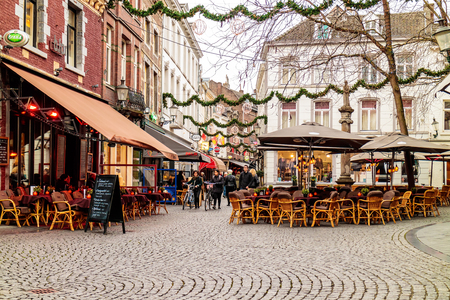 europeans: MAASTRICHT, THE NETHERLANDS - NOVEMBER 22, 2016: Dinner tables of bars and restaurants with christmas lights on the Sint Amorsplein square in Maastricht, The Netherlands