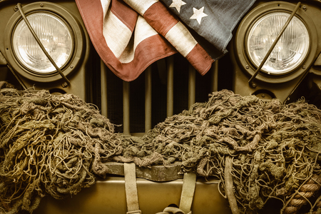 Retro styled image of an old army car with American flag
