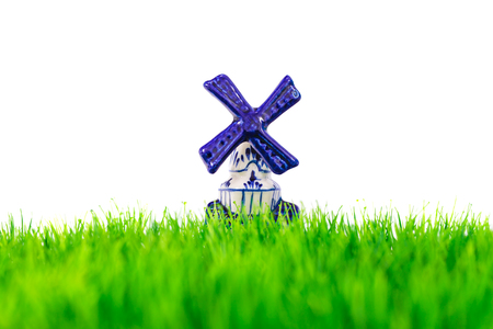 Dutch porcelain windmill in front of green grass isolated on a white background