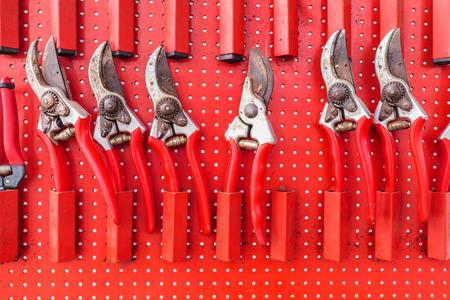 Fila de rojo utilizado tijeras de jardín colgando de una tabla de almacenamiento de herramientas de jardín
