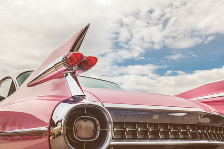 Retro styled image of the rear end of a pink classic car Stockfoto