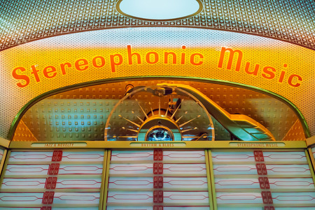 Close up of a vintage jukebox with empty labels and lights on