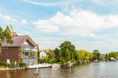 OUDERKERK AAN DE AMSTEL, NEDERLAND - 7 augustus 2017: Zomer uitzicht op de Amstel met huizen en boten in het kleine Nederlandse dorp Ouderkerk aan de Amstel, Nederland