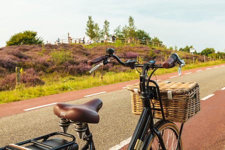 RHEDEN, THE NETHERLANDS – AUGUST 25, 2017: Electric black cargo bicycle with basket in front of the Veluwe Posbank with tourists in Rheden, The Netherlands Editorial