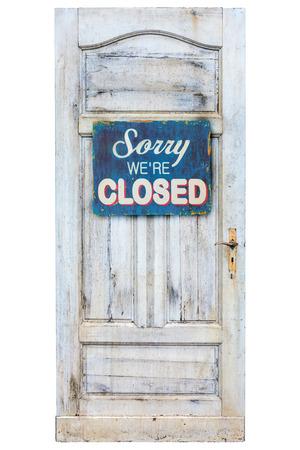 Verweerde houten deur met sorry we zijn gesloten teken