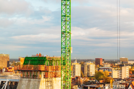GRONINGEN, THE NETHERLANDS - NOVEMBER 2, 2017: Construction workers on top of a high building next to the Grote Markt square in Groningen, The Netherlands