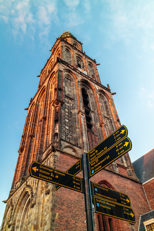 The famous Martinitoren church tower in Groningen with tourist guidance signs in front Redactioneel