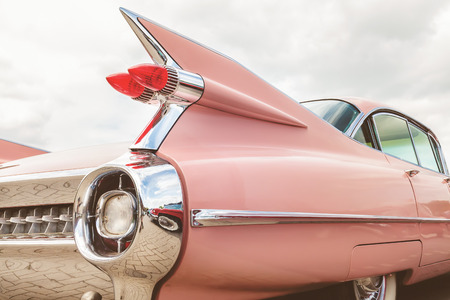 DEN BOSCH, THE NETHERLANDS - MAY 14, 2017: Retro styled rear end of a classic pink Cadillac fifties car in Den Bosch, The Netherlands