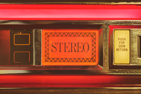 Close up of a vintage jukebox with the text stereo highlighted with red light