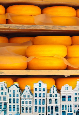 Dutch cheese ripening on wooden shelfs with Delft souvenir houses in front Stock fotó