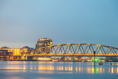 Railway bridge, apartments, houses and offices in the Dutch city of Nijmegen with the flooded river Waal in front Stock Photo