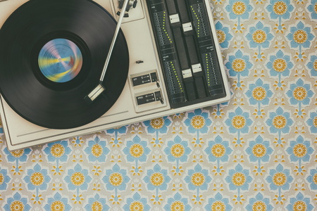 Retro styled image of an old record player on top of flower wallpaper Stockfoto