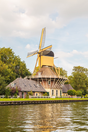 Ancient wooden windmill in front of a river in the village of Weesp