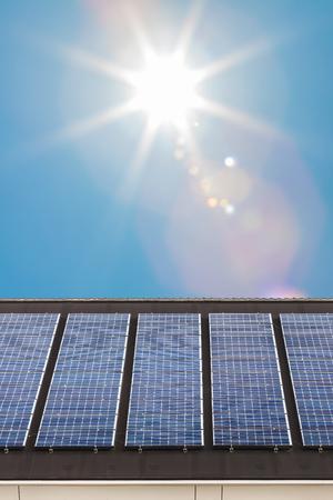 Fila de nuevos paneles solares en el techo de una casa Duth con el sol brillando en el fondo Foto de archivo