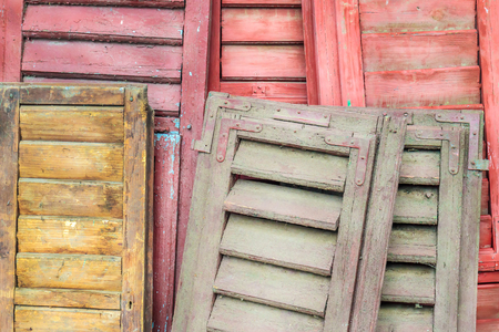 Stack of weathered louver doors on an antiques market