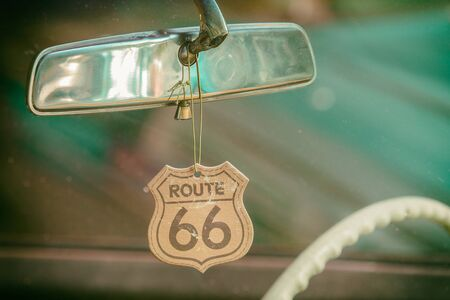 Route 66 badge hanging on a car mirror of a classic car