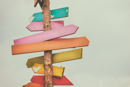 Colorful wooden direction arrow signs on a wooden pole