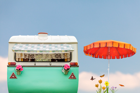 Vintage rear of a caravan in two tone green and white with parasol, flowers and butterflies