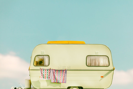 Retro styled image of a vintage caravan with towel and curtains