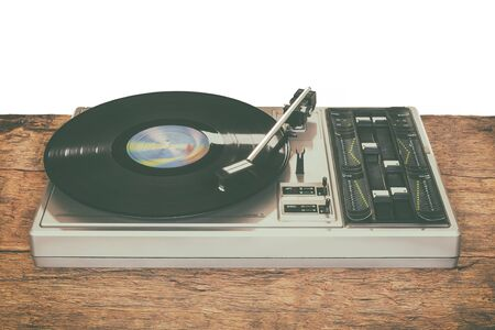 Old record player on a wooden table isolated on a white background