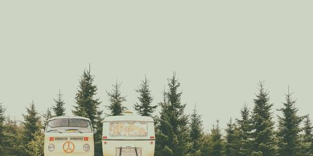 Retro styled image of a vintage camper and caravan in a forest