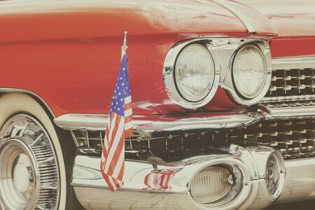 Classic red front of an old car with the American flag attached to the bumper grille