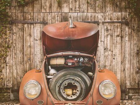 Rusted red classic car with open hood in front of an old barn door