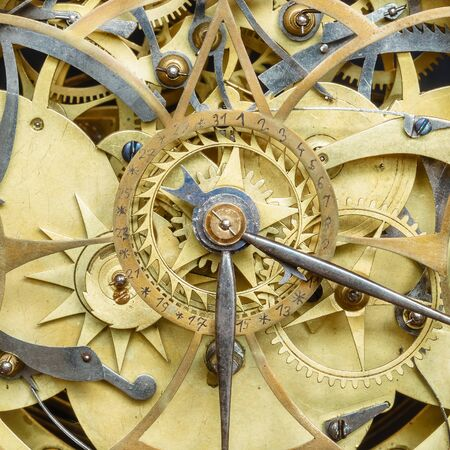 Innerworks of an antique clock with gear wheels and hour and minute hand Standard-Bild