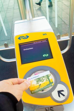 Apeldoorn, The Netherlands - November 11, 2019: Commuter holding railway card in front of a train automated check-in on the Dutch railway station of Apeldoorn, The Netherlands