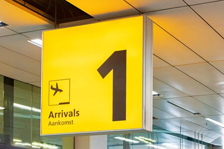 Dutch yellow airport arrival sign with the text 'arrival' in both english and dutch