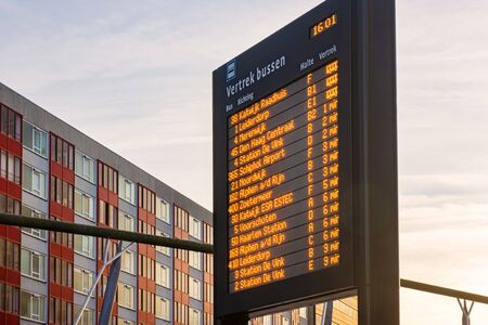 Information panel with Dutch bus departure times at Leiden Central Station, The Netherlands Stock Photo