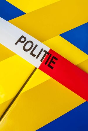 Red with white crime scene tape with the Dutch text 'police' on a police car